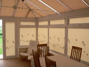 Roller blinds with flowers in conservatory