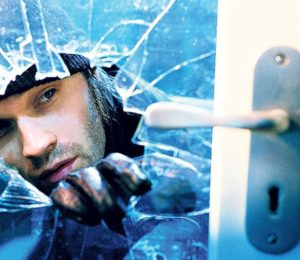 Burglar breaking glass
