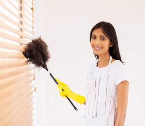 A lady is cleaning the wooden Venetian blinds